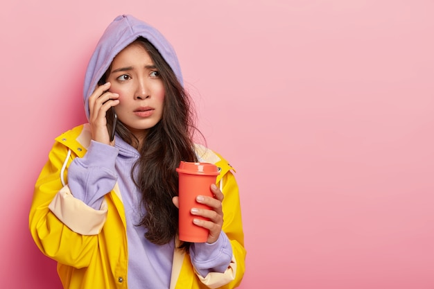 Displeased asian woman with rosy cheeks, has nervous face expression, calls boyfriend via smartphone, tries to warm herself with takeaway coffee