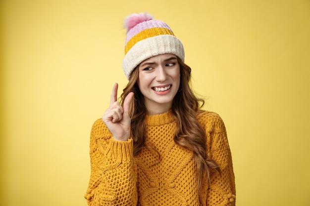 小さなオブジェクトを説明する不機嫌な魅力的なうるさい女性は、小さなものがしわくちゃになり、嫌いな失望を見て、指を動揺させ、少しの給料の新しい仕事を説明し、黄色の背景をぎこちなく立っています