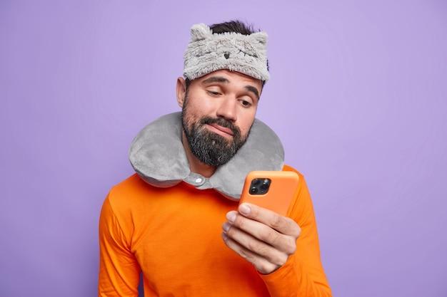 Недовольный бородатый взрослый мужчина с дорожной подушкой и маской для сна планирует, что его поездка использует мобильный телефон, озадачило недовольное выражение лица.