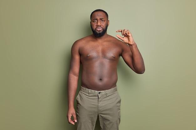 不機嫌なひげを生やしたアフリカ系アメリカ人の男性が裸の胴体でポーズをとる小さなもののジェスチャーが濃い緑の壁に対して非常に小さなオブジェクトのポーズを表示する
