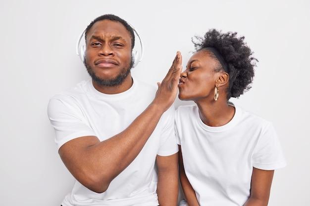 Displeased bearded afro american man refuses girlfriends kiss keeps palm forward her lips
