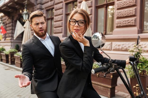 Displeased bearded business man sitting on modern motorbike outdoors