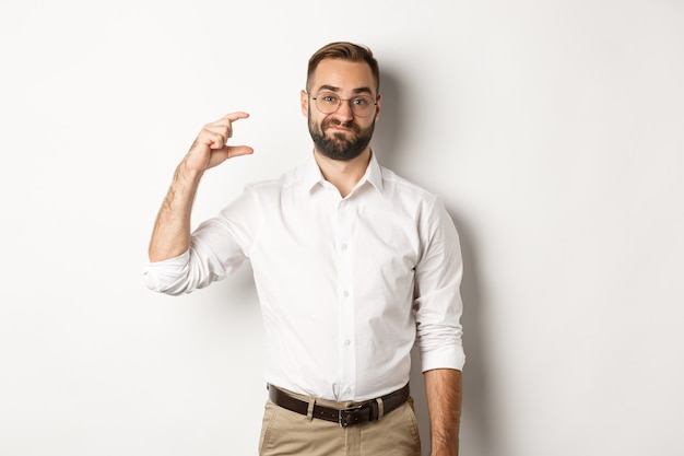 Displeased bearded businessman showing small gesture, looking disappointed, standing against white background.