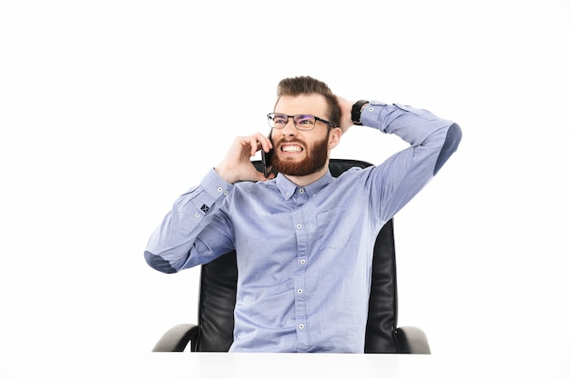 Недовольный бородатый элегантный мужчина в очках разговаривает со смартфоном, сидя за столом