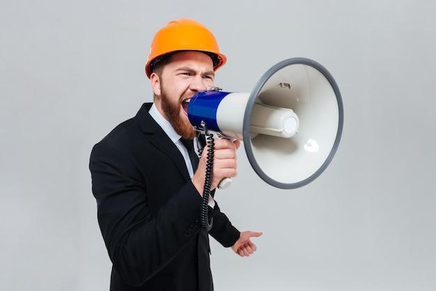 Displeased bearded engineer in black suit and orange helmet shouting in megaphone and looking aside.
