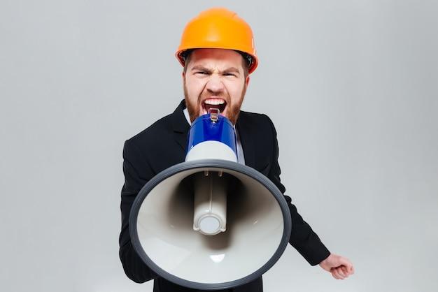 Displeased bearded engineer shouting in megaphone