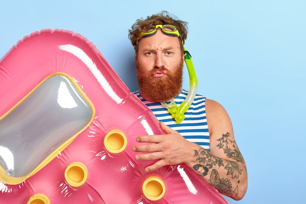 Displeased bearded guy poses with pink air mattress, wears swimming goggles and diving mask