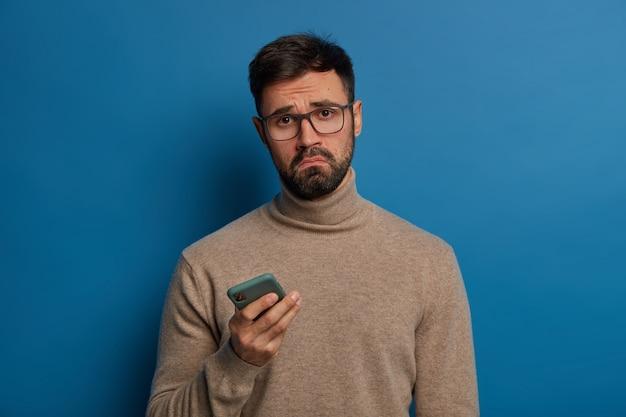 불쾌한 수염 난 남자는 얼굴을 웃으며, 현대적인 휴대폰을 사용하고, 슬픈 표정을 지으며, 투명한 안경과 점퍼를 착용합니다.