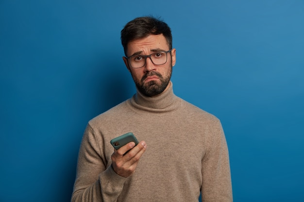 Displeased bearded guy smirks face, uses modern cellphone, has sad expression, wears transparent glasses and jumper