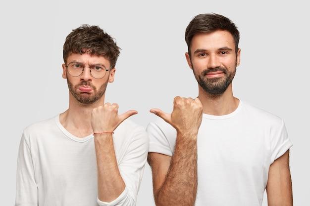 Недовольный бородатый мужчина чувствует себя обиженным на плохие шутки друга, указывает друг на друга, о чем-то спорит, одетый в повседневные белые футболки. люди, отношения, дружба