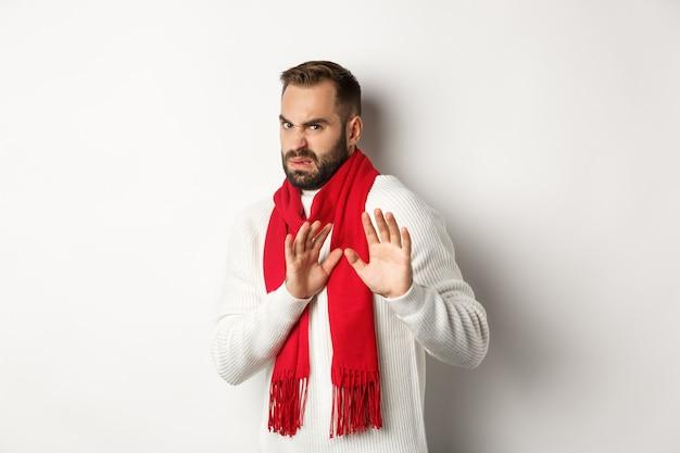 Uomo barbuto dispiaciuto che chiede di stare lontano, mostra il declino e ferma il gesto, si astiene da qualcosa di brutto, in piedi su sfondo bianco