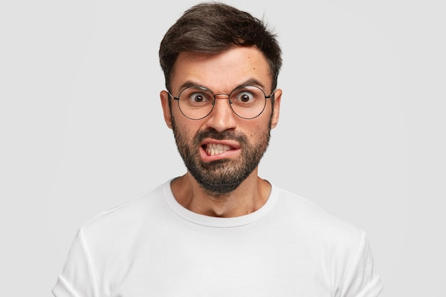 L'uomo barbuto scontento aggrotta le sopracciglia con dispiacere, ha un'espressione irritata, alza le sopracciglia e stringe i denti