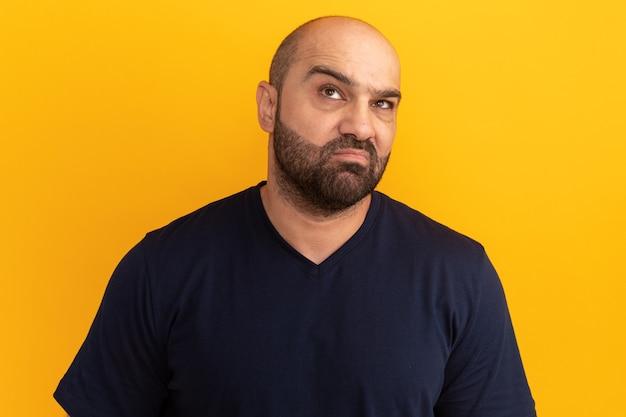 Uomo barbuto scontento in maglietta blu scuro che osserva in su facendo la bocca ironica con espressione delusa in piedi sopra la parete arancione