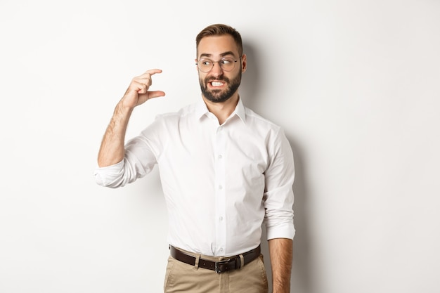 Displeased bearded man showing small gesture, looking disappointed, standing against white background.