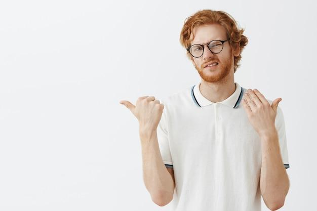 眼鏡をかけて白い壁にポーズをとって不機嫌なひげを生やした赤毛の男