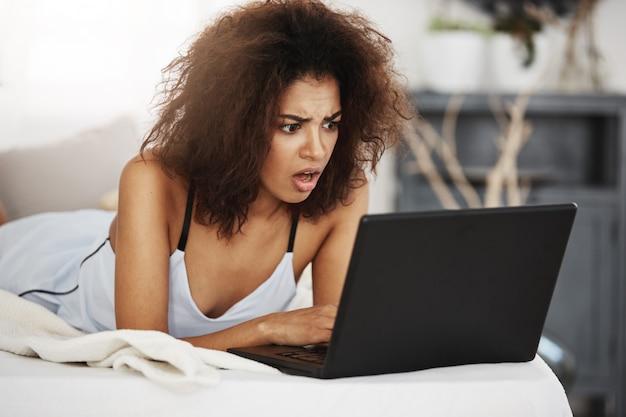 Раздражанная красивая африканская женщина в одежде для сна смотря компьтер-книжку лежа на кровати дома.