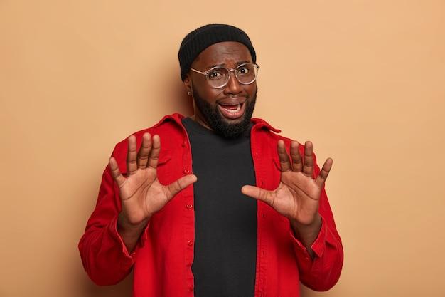 불쾌한 흑인 남자는 손바닥을 앞으로 카메라를 유지하고 중지 또는 거부 신호를 만듭니다.