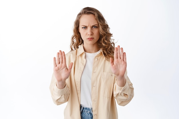 Displeased blond woman frowning, showing stop block gesture, refusing offer, say no and reject something bad, standing over white wall