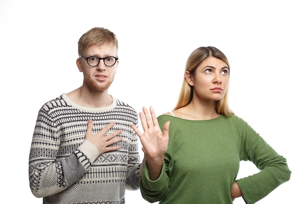 Displeased blonde girl showing stop sign with her palm, meaning it's over while her unhappy miserable boyfriend with unhappy look holding hand on his chest as sign of broken heard