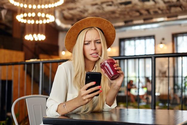 Раздосадованная голубоглазая молодая длинноволосая блондинка держит мобильный телефон в руке и смотрит на экран с надутым лицом, хмурясь и показывая свои белые идеальные зубы