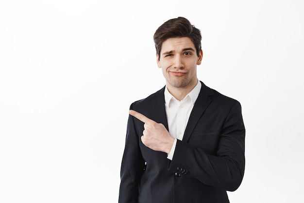 Displeased boss, businessman in black suit frowning and shaking head upset with bad result, pointing left with skeptical face, standing disappointed against white wall
