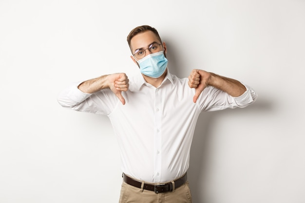 Displeased boss wearing face mask and showing thumbs down, dislike and disapproval sign, white background.