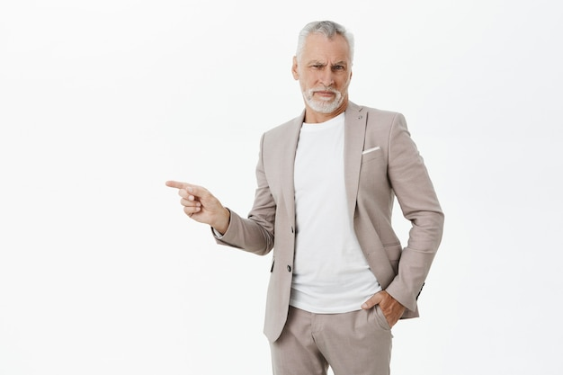 不機嫌な人差し指を左に向けてスーツを着たビジネスマンを悩ませ、顔をゆがめた