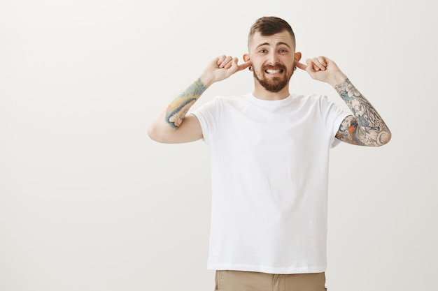 Displeased and bothered hipster guy shut ears from loud annoying noise