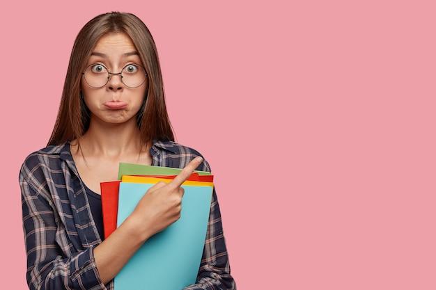 不機嫌なブルネットの女性は攻撃で下唇を財布に入れ、丸い眼鏡を通して無知に見えます、脇を指します