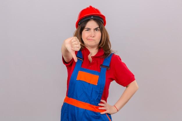 Недовольная женщина-строитель в строительной форме и защитном шлеме показывает большой палец вниз с хмурым лицом, стоящим над изолированной белой стеной