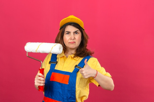 Displeased builder woman wearing construction uniform and yellow cap holding paint roller in hand showing thumb up over isolated pink wall