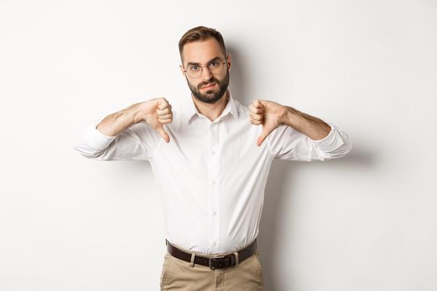 親指を下に向けて、嫌いで不承認になり、白く立っている眼鏡をかけた不機嫌なビジネスマン