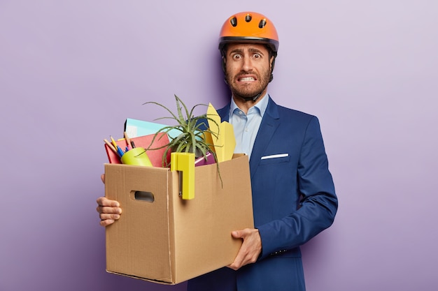 Imprenditore scontento in posa in abito di classe e casco rosso in ufficio