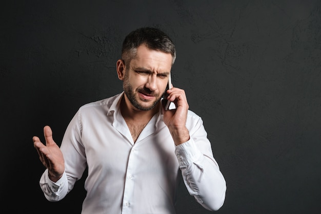 Displeased businessman talking by mobile phone.