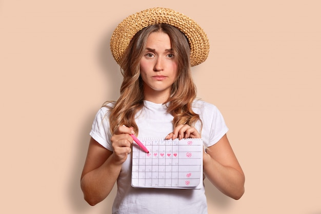 Displeased caucasian female in casual t shirt and straw hat, indicates at period calendar, doesnt want to have menstruation during rest at seaside, isolated on beige. unhappy woman indoor