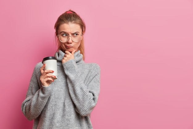 불쾌한 백인 소녀는 불행한 표정으로 깊이 생각하고, 턱과 지갑을 만지며, 성가신 상황을 해결하는 방법을 생각하고, 회색 스웨터를 입습니다.