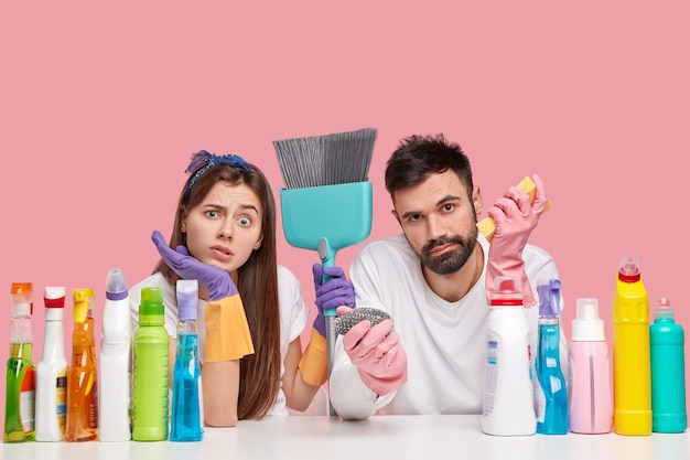 Displeased caucasian woman and man look with displeasure, feels fatigue after spring cleaning in house, use broom