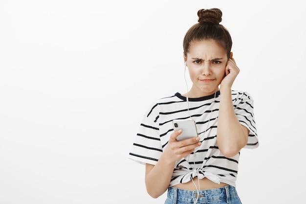 실망하고, 끔찍한 음악이나 팟 캐스트를 이어폰으로 듣고, 휴대 전화를 들고 불만을 품은 불평하는 소녀