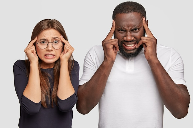 Displeased concentrated mixed race woman and man have dissatisfied facial expressions, keep index fingers on temples
