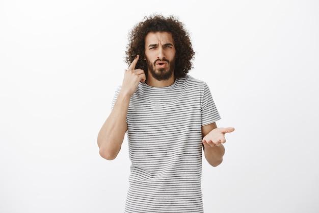 Scontento studente maschio barbuto confuso in maglietta a righe, indicando l'orecchio e accigliato, non può sentire la domanda mentre è in compagnia ad alta voce