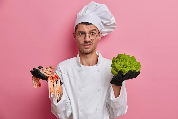 Cuoco scontento in uniforme bianca, lavora al ristorante, incaricato di cucinare piatti di broccoli e gamberi, indossa guanti neri