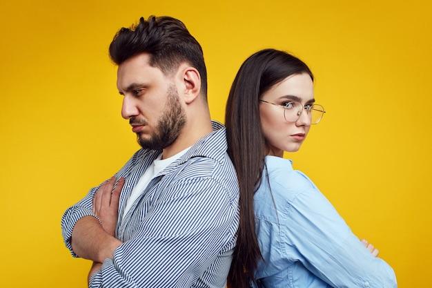 Недовольная пара со скрещенными руками борется спиной к спине