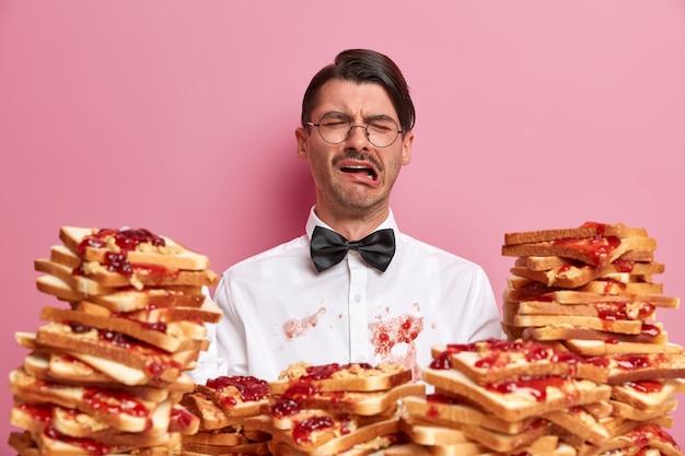 Недовольно плачущий мужчина в грязной белой рубашке, неосторожно ел хлеб, выражает негативные эмоции, носит элегантную одежду, у него неудачный день, посещает кафе или ресторан, изолирован на розовой стене