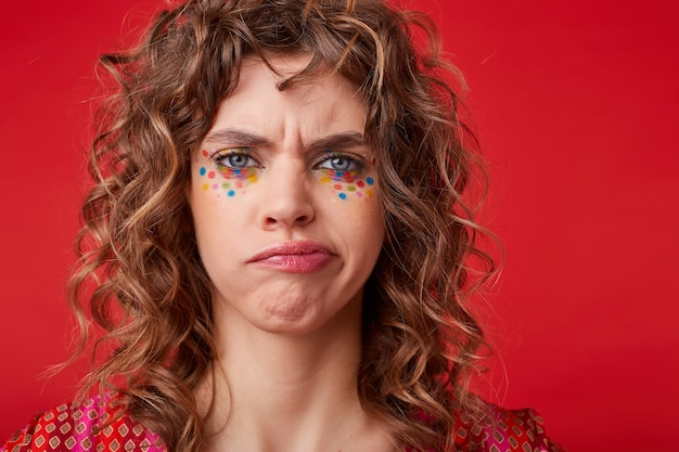 Dispiaciuta riccia femmina dagli occhi azzurri con punti multicolori sul viso torcendo la bocca con le sopracciglia accigliate, in piedi con una smorfia insoddisfatta