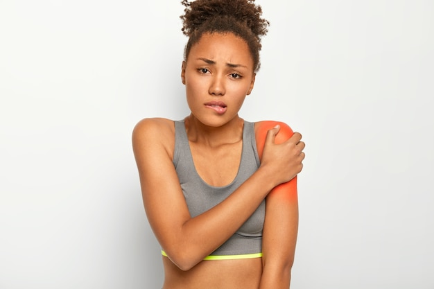 Displeased curly haired woman bites lips, touches painful shoulder, suffers from injury, wears grey top, isolated on white background. health problems, medical concept