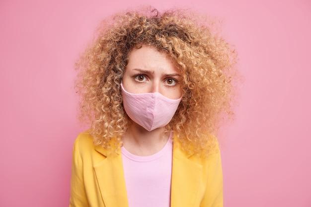 불쾌한 곱슬 머리 여자는 코로나 바이러스 확산 동안 완전히 보호되는 마스크로 코와 입을가립니다. 자기 격리에 외로움을 느낍니다. 분홍색 벽 위에 고립 된 공식적인 노란색 재킷을 입습니다.