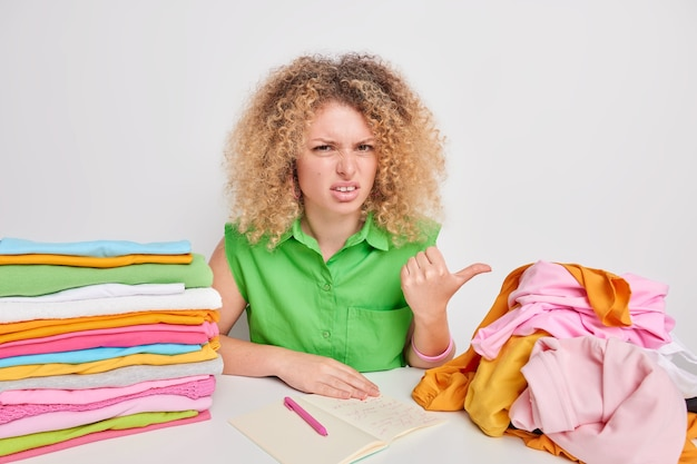 Displeased curly haired woman points with thub at unfolded laundry feels tired of domestic work makes notes in notepad writes down washing temperature for clothes made of different material.