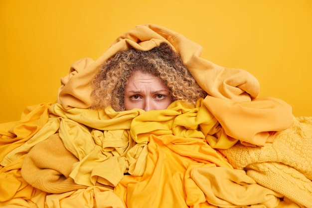 Displeased curly haired young woman buried in heap of unfolded clothes collected for recycling or donation has frustrated look isolated over yellow