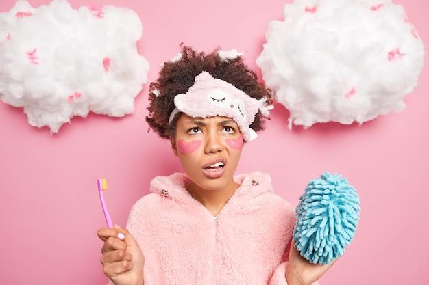 불쾌한 곱슬 머리의 젊은 여성이 얼굴을 능글 맞이하고 위의 불행하게 보이는 눈 아래 콜라겐 패치를 적용하는 것은 아침 루틴이 분홍색 벽 위에 절연 목욕 스폰지 칫솔을 보유하고 싫어합니다.