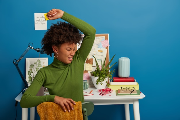 Displeased curly woman smells unpleasant stinch under armpit, wears green turtleneck, sits over coworking space, prepares for examination session in own cabinet, feels tired.